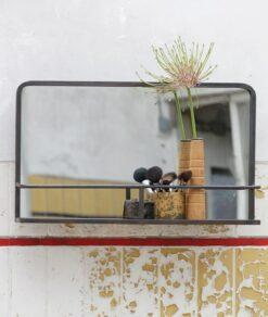 Leuke foto van deze spiegel met producten in zijn opslagbakje van een afstand
